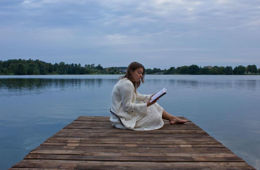 Kvinde læser på badebro