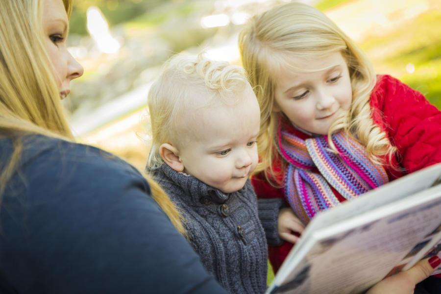 Billede af en mor, der læser op for sin to børn