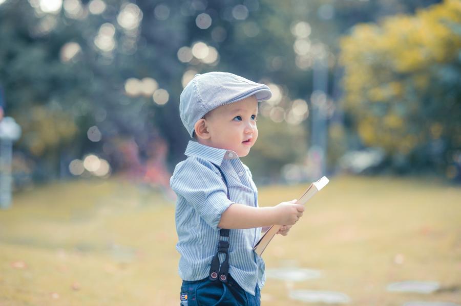 Lille glad dreng der læser i en bog
