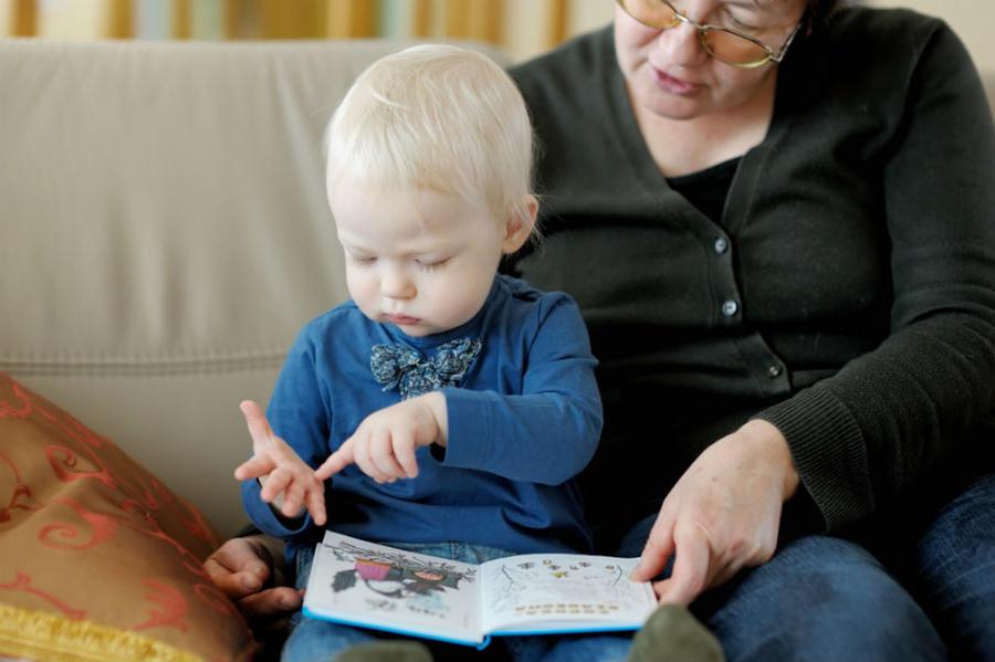 En voksen og et barn læser i en bog sammen