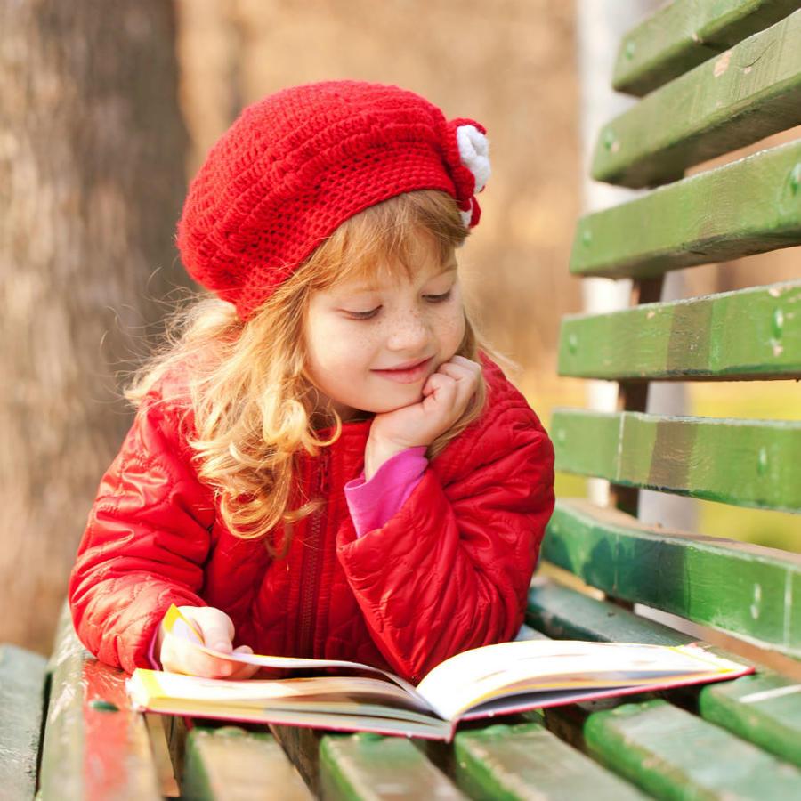 Lille pige ligger på en bænk og læser