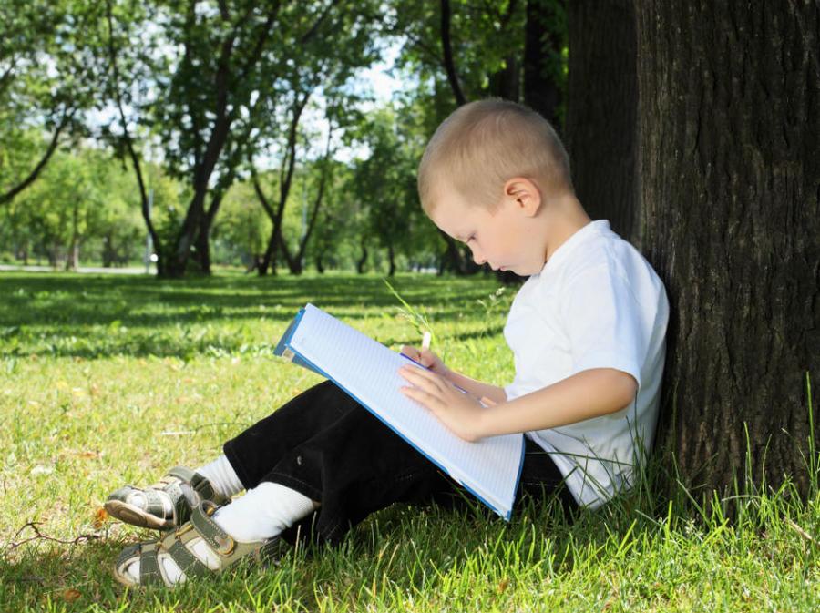 En dreng sidder under et træ og læser i en bog