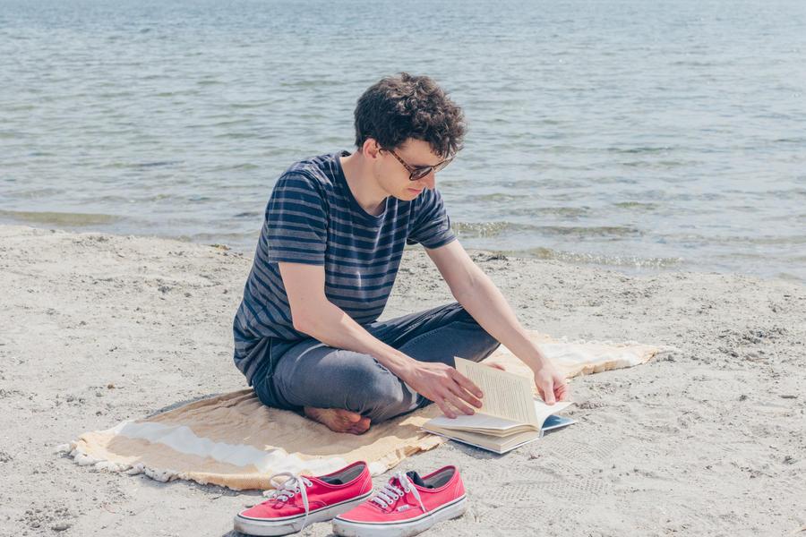 Mand læser på strand