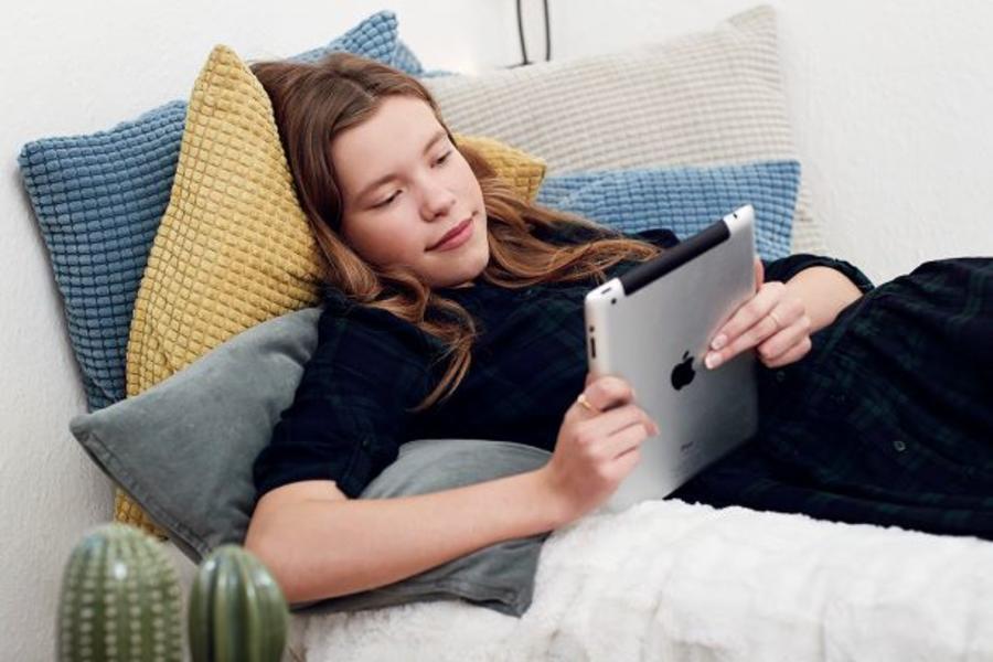 Pige ligger og læser en ebog