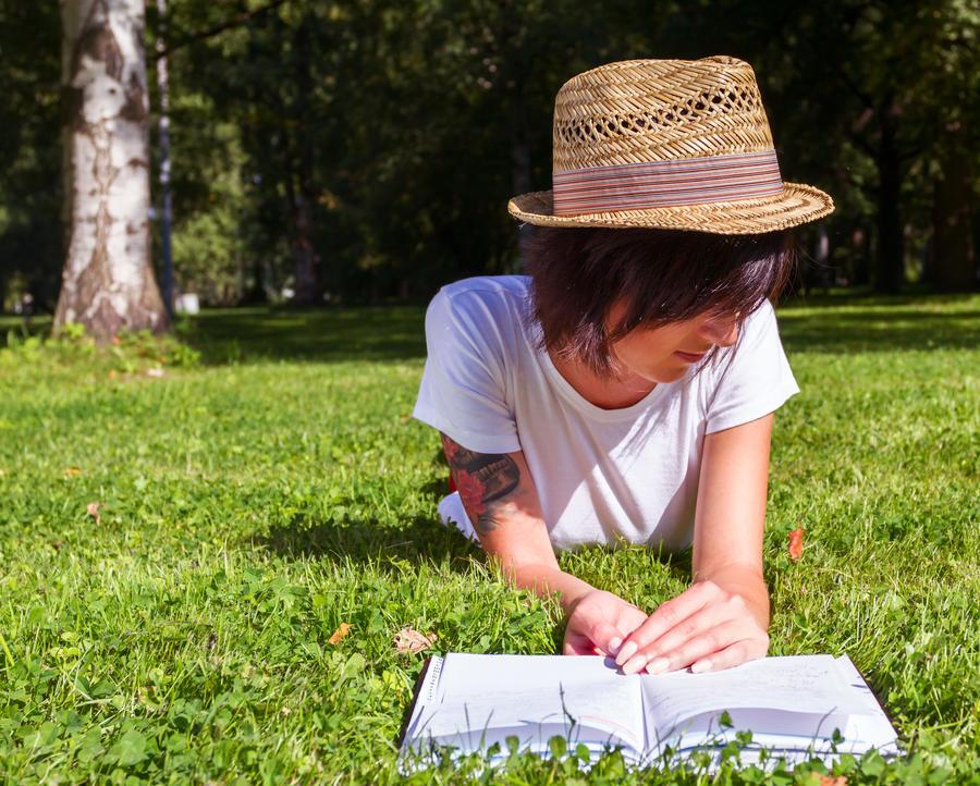 Ung pige ligger i græsset og læser