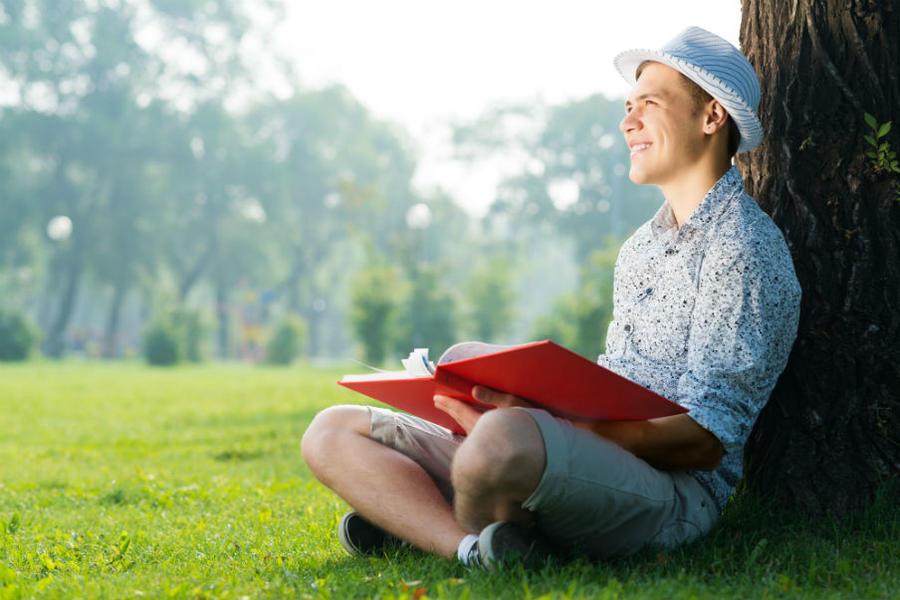 Ung mand sidder under et træ med en bog