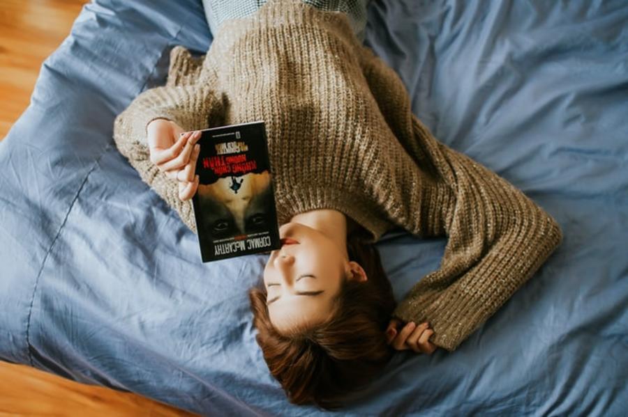 Ung pige ligger på gulvet og læser en bog