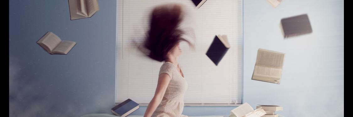 Kvinde på en senge med flyvende bøger omkring sig